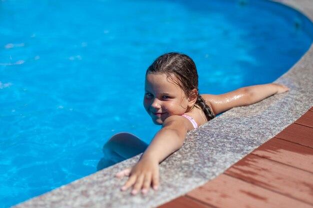 笑顔の5歳の女の子がホテルのプールの端に手を大きく置いて...