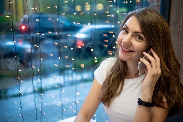 カフェのノートパソコンで働いて電話で話している笑顔のフリーランスの女の子、無料の若い女性や学生の就業日。