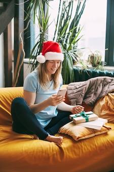 クリスマスの帽子をかぶった笑顔の女の子がソファに座って、友達と電話で話している
