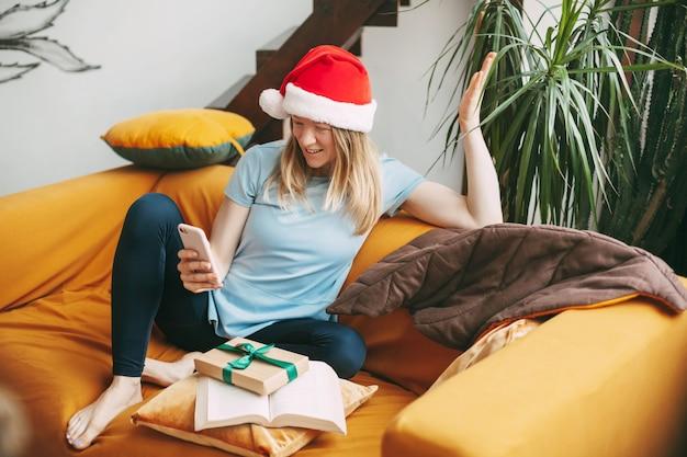 クリスマスの帽子をかぶった笑顔の女の子がソファに座って、ビデオリンクを介して友達と通信します