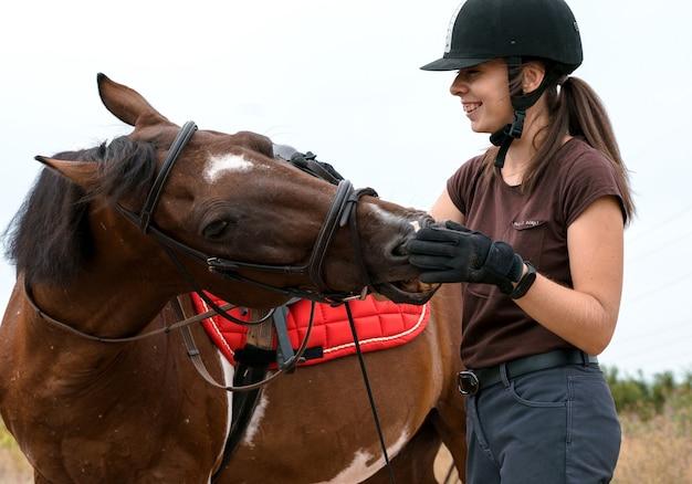 Улыбающаяся девушка в шлеме для верховой езды общается со своим пегим конем