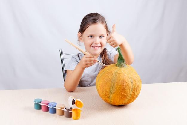 Улыбающаяся девушка на белой стене рисует тыкву из папье-маше и показывает палец вверх