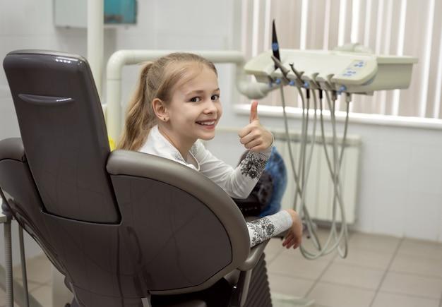 웃는 소녀가 치과 의자에 앉아 엄지 손가락을 올려줍니다.
