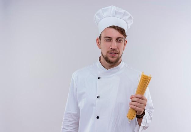白い壁を見ながらスパゲッティを保持している白い炊飯器の制服と帽子を身に着けている笑顔のハンサムな若いひげを生やしたシェフの男