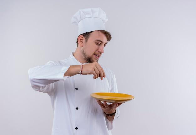 Улыбающийся красивый молодой бородатый повар в белой униформе и шляпе держит желтую тарелку на белой стене