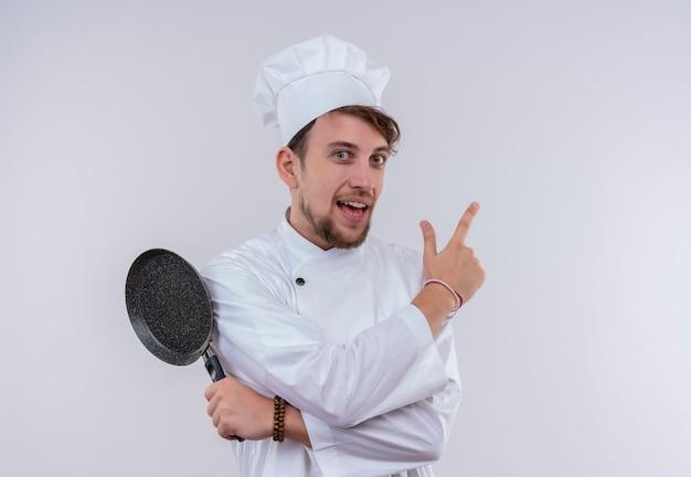 白い炊飯器の制服と帽子をかぶって、白い壁を見ながらフライパンを上向きに保持している笑顔のハンサムな若いひげを生やしたシェフの男