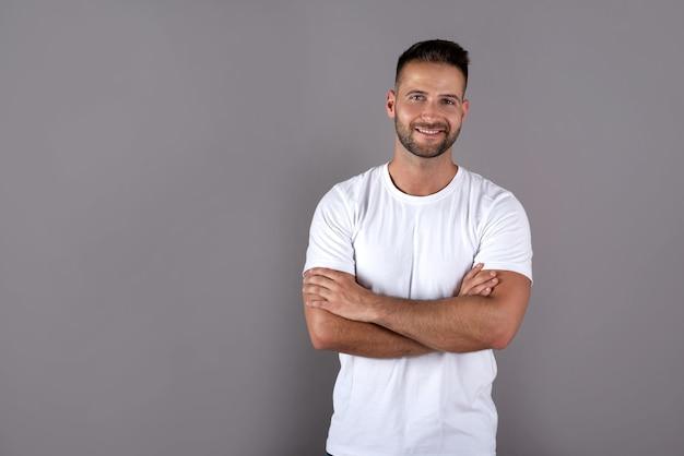 Улыбающийся красивый молодой человек в белой футболке стоит на сером