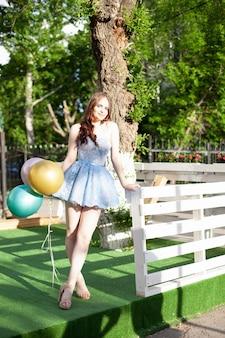 Улыбающаяся счастливая женщина в праздничном коротком синем корсетном платье стоит на открытой террасе