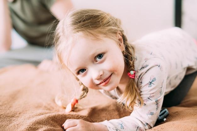 Улыбающийся маленький ребенок со светлыми волосами лежит на кровати у себя дома на одеяле и смотрит в камеру