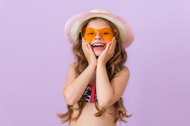 수영복과 모자를 쓴 웃는 어린 소녀가 뺨에 손을 얹고 있습니다.