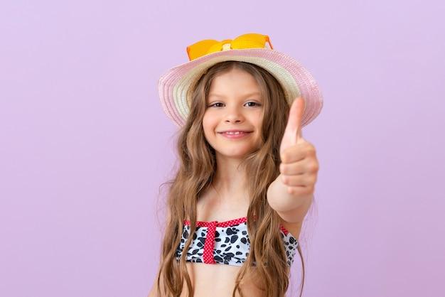 외진 배경에 수영복을 입은 웃는 어린 소녀가 엄지손가락을 치켜듭니다.