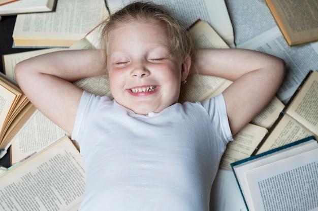 Улыбающаяся маленькая девочка лежит с закрытыми глазами на кучу открытых книг. вид сверху. образование и обучение. крупный план.