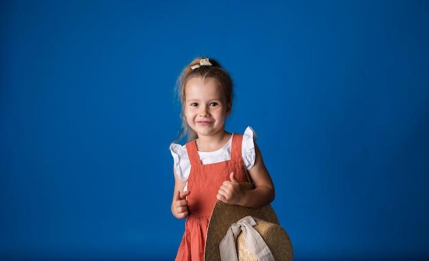 밀짚 모자와 함께 웃는 어린 소녀 약자와 텍스트를위한 공간이있는 파란색 표면에 카메라를 찾습니다