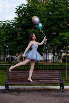 青い短いコルセットのドレスを着た笑顔の足の長い若い女性は、ベンチの上を裸足で歩き、flを保持します...