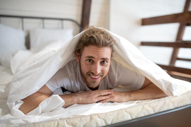毛布で身を包む笑顔の男