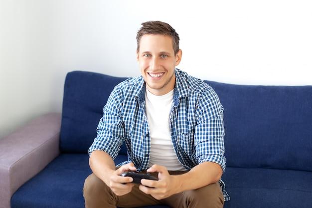 Улыбающийся человек в рубашке, сидя на диване, играет в видеоигру с джойстиком. gamer.