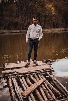 白いシャツを着た笑顔の男が川の近くの木造の破壊された桟橋に立っています