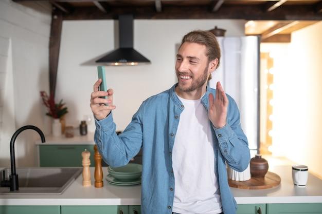 Улыбающийся человек записывает видеообращение дома