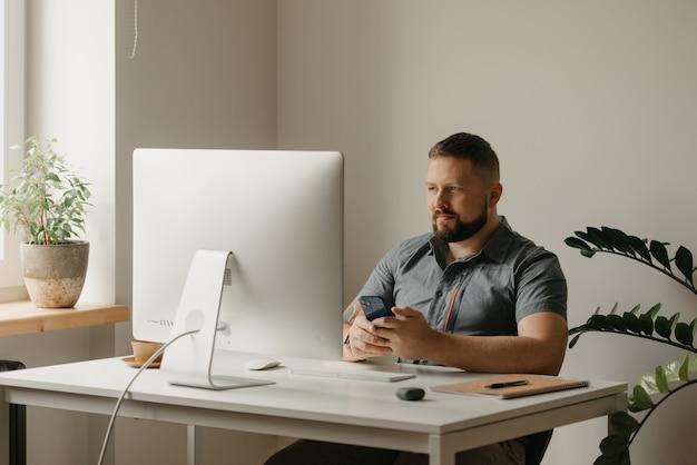 웃는 남자가 데스크톱 컴퓨터에서 원격으로 작업합니다. 수염을 기른 한 남자가 집에서 화상회의를 하고 있는 동료의 보고 중에 핸드폰을 들고 있다. 교사가 온라인 강의를 준비하고 있습니다.
