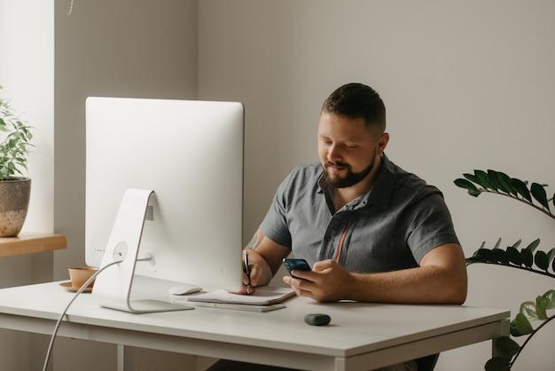 웃는 남자가 데스크톱 컴퓨터에서 원격으로 작업합니다. 수염을 기른 남자가 집에서 메모를 하고 휴대폰을 들고 있다. 한 교사가 온라인 강의를 준비하고 있습니다.