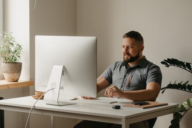 웃는 남자가 데스크톱 컴퓨터에서 원격으로 작업합니다. 수염을 기른 남자가 집에서 화상 회의를 하고 있는 동료의 보고 중에 타이핑을 하고 있습니다. 한 교사가 온라인 강의를 하고 있습니다.
