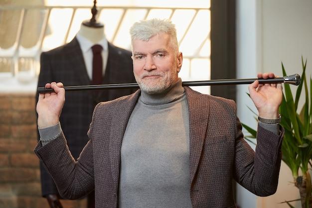 白髪とスポーティな体格の笑顔の成熟した男は、衣料品店で彼の頭の後ろに両手でファイバーカーボン杖を持っています。あごひげを生やした男性客がブティックでスーツを着ています。