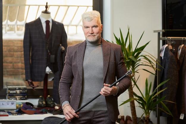白髪とスポーティな体格の笑顔の成熟した男は、衣料品店で両手でファイバーカーボン杖を持っています。あごひげを生やした男性客がブティックでスーツを着ています。