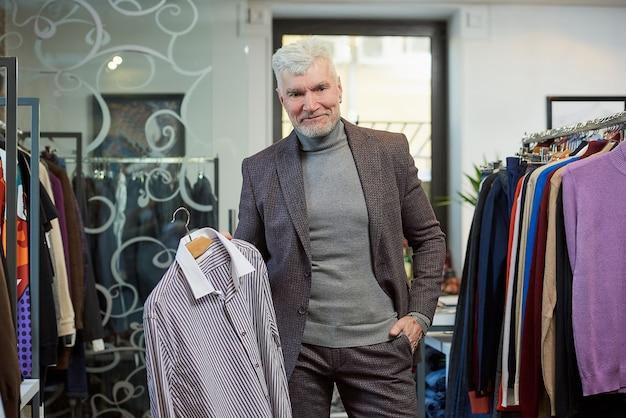 白髪とスポーティな体格の笑顔の成熟した男が、衣料品店でポーズをとってシャツを見せています。あごひげを生やした男性客は、ブティックでウールのスーツを着ています。