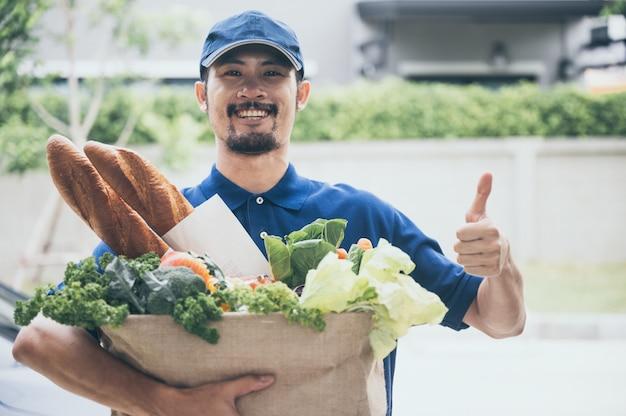 웃고 있는 남성은 고객의 집에 식료품을 빠르고 신속하게 배달하고, 코로나바이러스 코비드-19 검역 기간 동안 온라인 쇼핑, 친환경 종이 봉지에 담긴 음식, 마음으로 일합니다