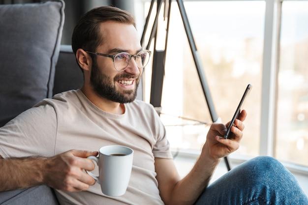 携帯電話を使用してコーヒーを飲みながら自宅で笑顔の楽観的な若い男。