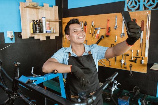 자전거를 수리하는 동안 휴대 전화를 사용하여 셀카를 앞치마에 웃는 수리공