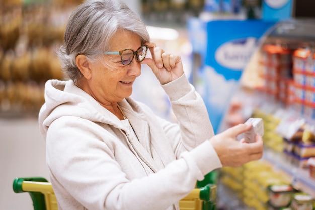 구매하기 전에 제품을 확인하는 슈퍼마켓에서 웃는 수석 여자.