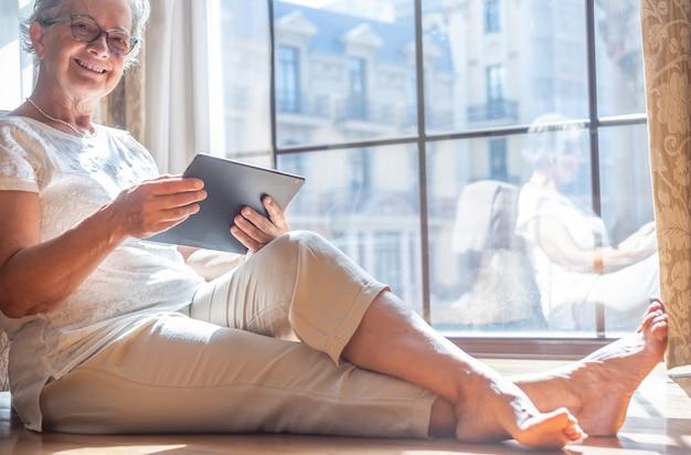 바르셀로나 여행을 즐기는 디지털 태블릿을 사용하여 호텔 방의 바닥에 앉아 웃고 있는 고위 여성. 그녀 뒤에 큰 창