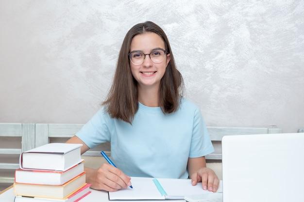 책이 있는 탁자에 앉아 웃고 있는 10대 학생이 공책에 과제를 작성하고 있습니다. 학교 개념으로 돌아가기. 홈 스쿨링 개념입니다.