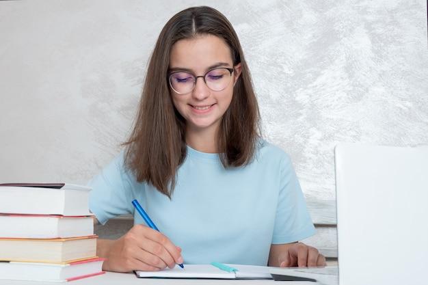 책이 있는 탁자에 앉아 웃고 있는 10대 학생이 공책에 과제를 작성하고 있습니다. 소녀는 대학, 고등학교 입학을 위해 공부하는 학생입니다. 홈 스쿨링 개념입니다.