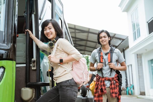 문 손잡이를 잡고 배낭과 헤드폰을 들고 웃는 여자가 버스에 탑승