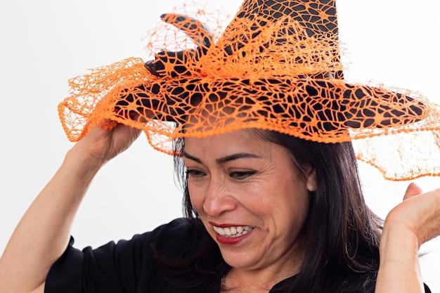 魔女の帽子を調整する魔女の衣装を着た笑顔の女性