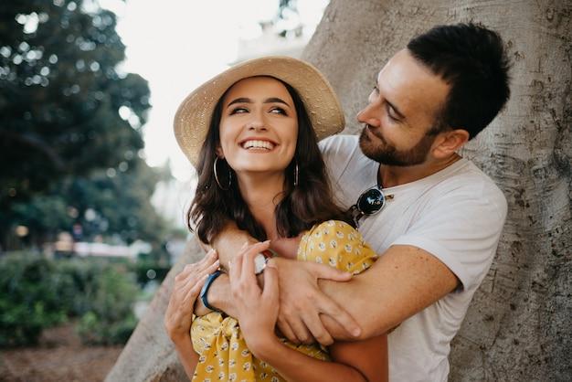 Улыбающаяся женщина в шляпе и желтом платье и ее счастливый парень с бородой обнимаются под старым валенсийским фикусом macrophylla в испании.