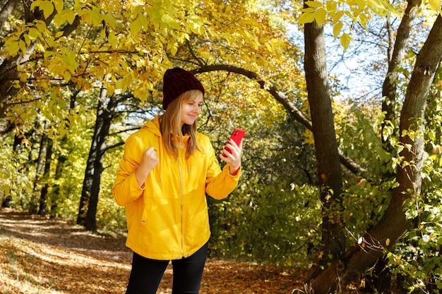 黄色いレインコートと紅葉を背景に赤い帽子をかぶった笑顔の女性が散歩中に電話で話します