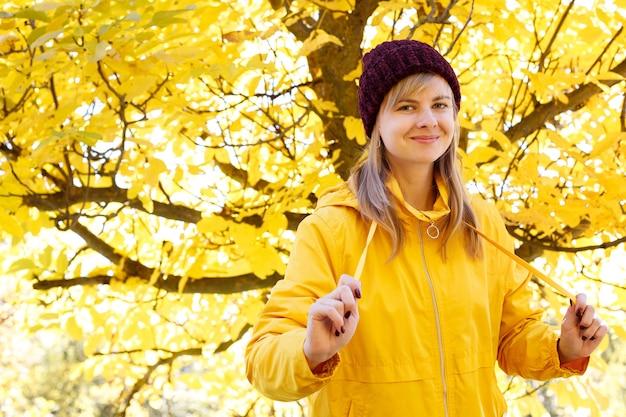 秋の散歩で黄色い秋の木の背景に黄色いレインコートと赤い帽子の笑顔の女性。横にテキスト用の空きスペース