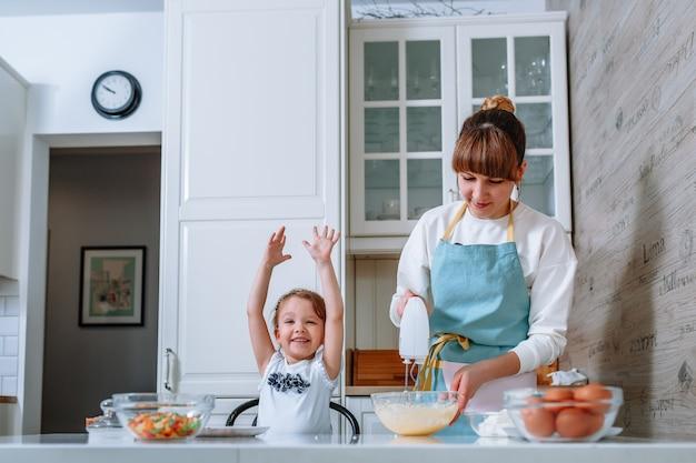 Улыбающаяся женщина счастлива, когда ее мать взбивает тесто миксером.