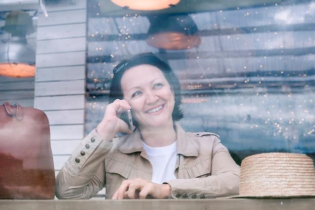 笑顔の女性がカフェのサマーテラスのテーブルに座って電話で話している。