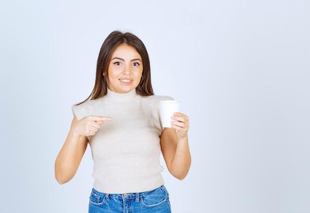 プラスチック製のコップを指してポーズをとる笑顔の女性モデル。