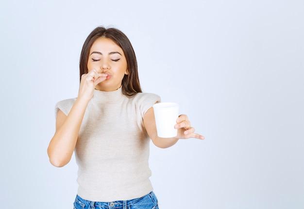Улыбающаяся модель женщины показывает пластиковый стаканчик и позирует.