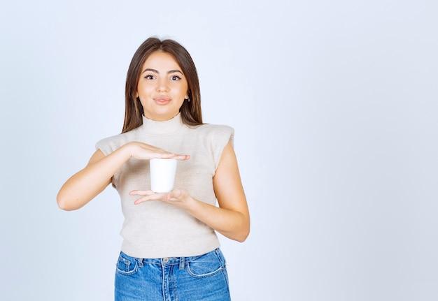 플라스틱 컵을 보여주는 포즈 웃는 여자 모델.
