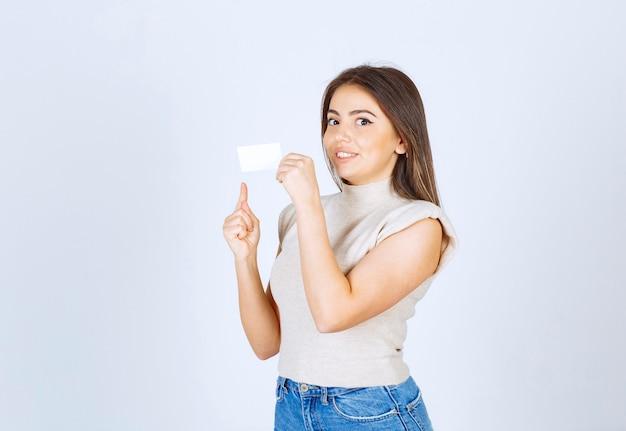 立って、白い背景の上のカードを指して笑顔の女性モデル。