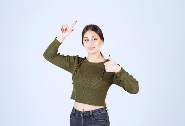 Улыбающаяся женщина указывает вверх указательным пальцем и показывает большой палец вверх.