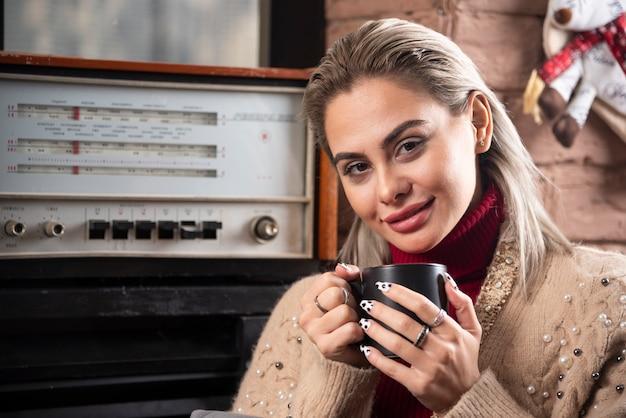 Улыбающаяся женщина сидит и держит чашку кофе