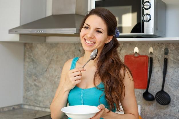Улыбающаяся женщина с темными волосами в синей футболке стоит на кухне с ложкой в руке