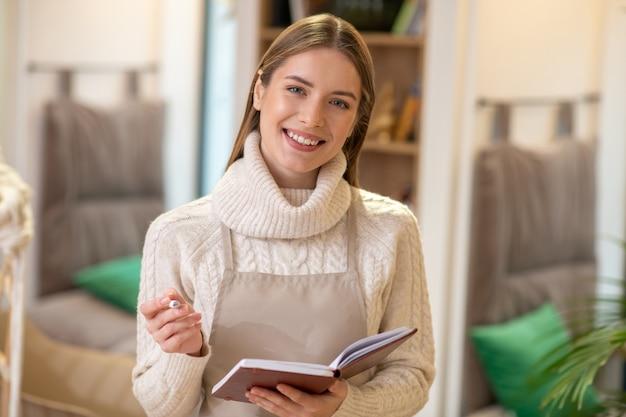 ノートに自分のアイデアを書いている笑顔の女性
